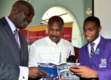 Chairman of the CARICOM Reparation Commission, Professor Hilary Beckles (centre), along with Principal, Kingston College, Dave Myrie (left) and Kingston College Head Boy, Chevon Lewis, peruse a copy of his book, 'Britain's Black Debt', following a lecture on reparation justice at the school on April 15. Photo: Mark Bell