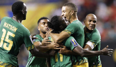 Jamaica's Darren Mattocks, center, is embraced by teammate Michael Hector after scoringa goal against the U.S. in the first half of a Gold Cup semifinal Wednesday in Atlanta.  (David Goldman / Associated Press)
