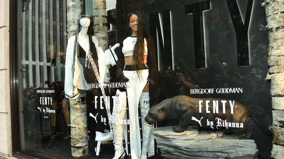 Rihanna playfully stands as a mannequin in Bergdorf Goodman's NYC store for Fenty x Puma launch