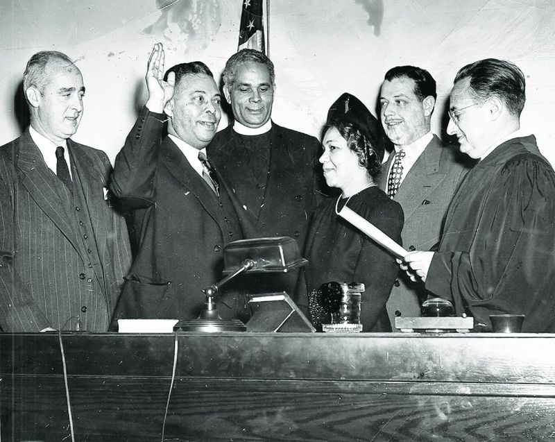 Hand raised, Bertram Baker is sworn in as member of the New York State Assembly by state Supreme Court Justice Ivan Rubenstein, on Dec. 21, 1948, as his wife, Irene, friend Lloyd Herzka (second from right), and the Rev. John Coleman look on. (Courtesy of Ron Howell family archives)